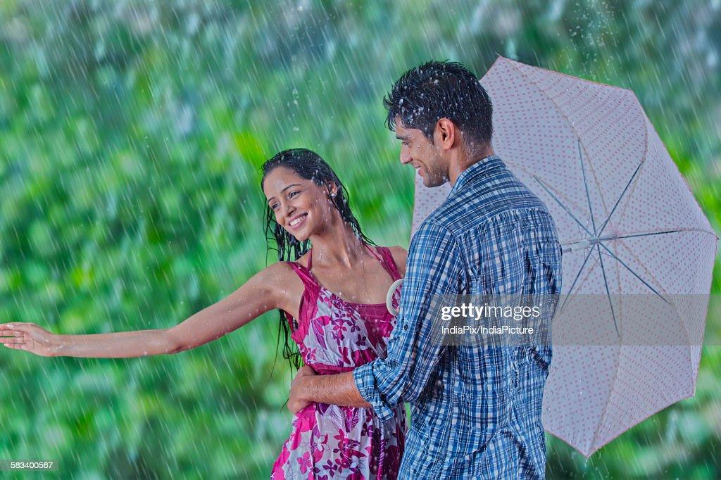 Couple enjoying in the rain : Stock Photo