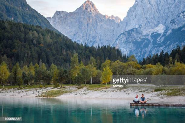 couple enjoying late afternoon scenic beauty at jasna lake - mid distance stock pictures, royalty-free photos & images