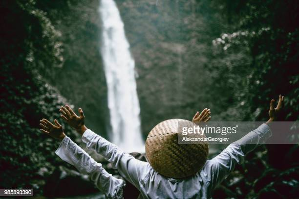 couple enjoying nature landscape near waterfall - indonesian culture stock pictures, royalty-free photos & images