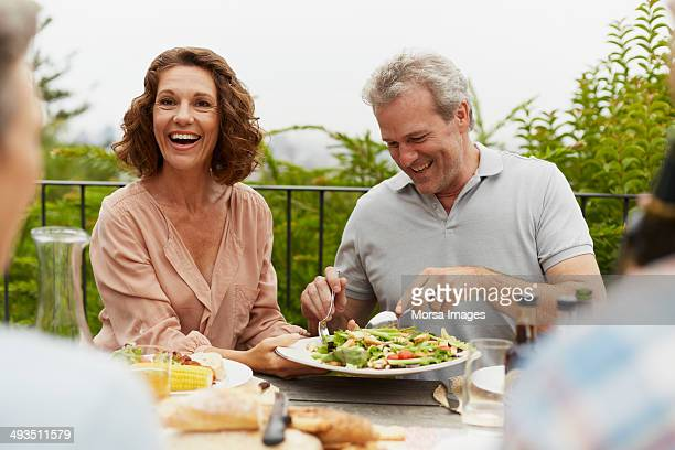 couple enjoying outdoor lunch with friends - 50 54 years stock pictures, royalty-free photos & images