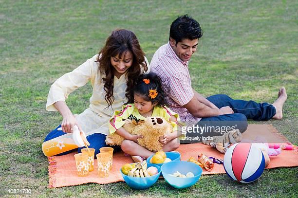 Couple enjoying picnic with their daughter, Gurgaon, Haryana, India