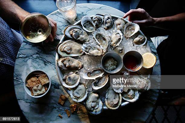 a couple enjoying raw oysters - seafood stock pictures, royalty-free photos & images