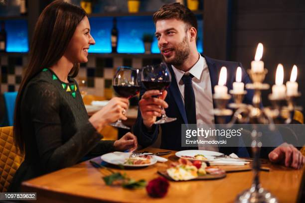 couple enjoying red wine on valentine's day - valentines day dinner stock pictures, royalty-free photos & images