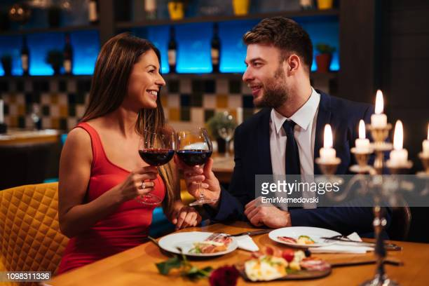 couple enjoying red wine on valentine's day - valentine's day holiday stock pictures, royalty-free photos & images