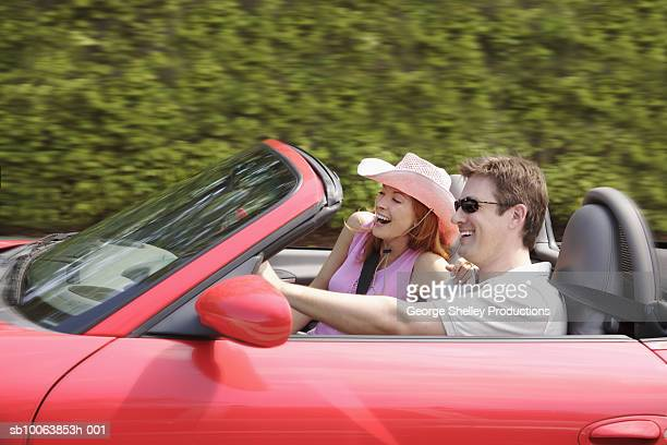 Couple enjoying ride in pink convertible