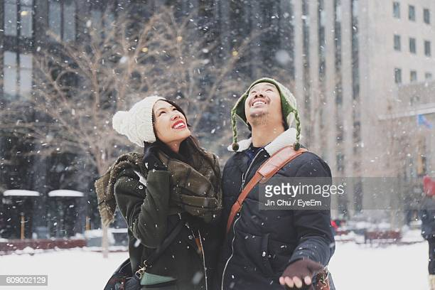 Couple Enjoying Snowfall During Winter In City