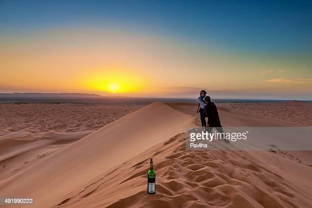 Pareja disfrutando de sol dunas de Erg Chebbi, Marruecos, África del Norte