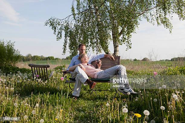 A couple enjoying sunshine and wine on a bench in their backyard