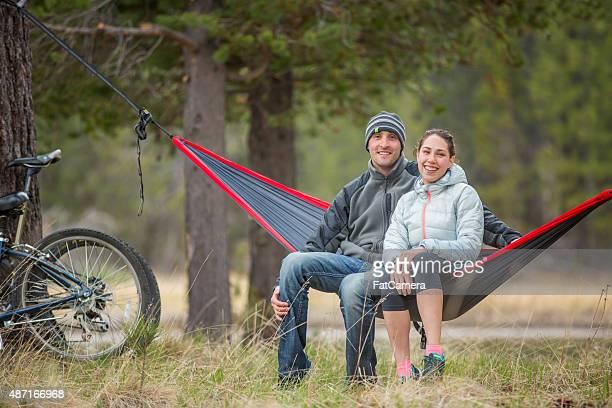 Couple enjoying the outdoors on a hammock