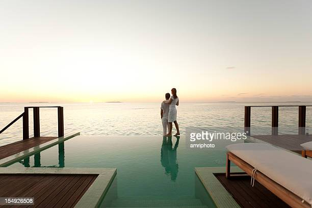 couple enjoying the sunset at poolside - luxury stock pictures, royalty-free photos & images