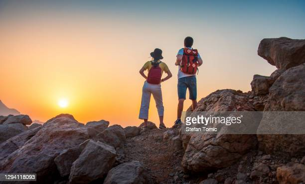 couple enjoying the view from the mountain top in the uae desert at sunset - ras al khaimah stock pictures, royalty-free photos & images