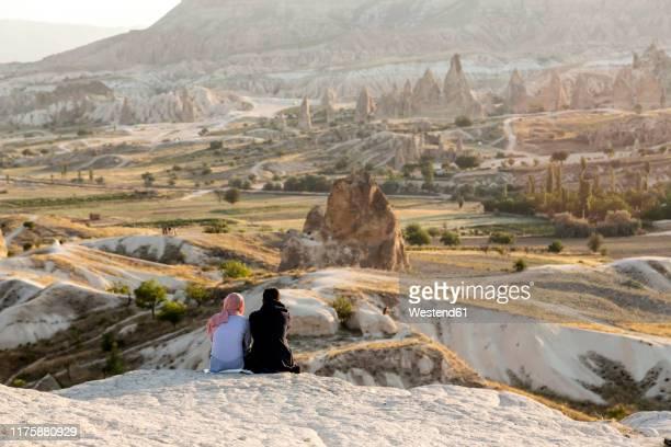 couple enjoying the view of rocky landscape at dusk, goreme, cappadocia, turke - アナトリア ストックフォトと画像