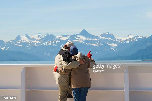 couple enjoying the view of snowy mountains from ship - heterosexual couple stock pictures, royalty-free photos & images