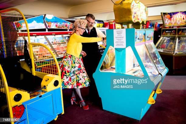 Couple enjoying themselves in amusement arcade, Bournemouth, England