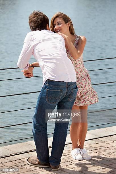 a couple enjoying time by a lake - côte à côte photos et images de collection