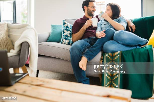 Couple enjoying time together while relaxing on sofa.