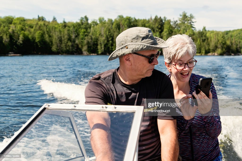 50+ couple enjoying vacations on a small boat. : Stock Photo
