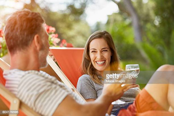 Couple enjoying wine while relaxing on deck chairs