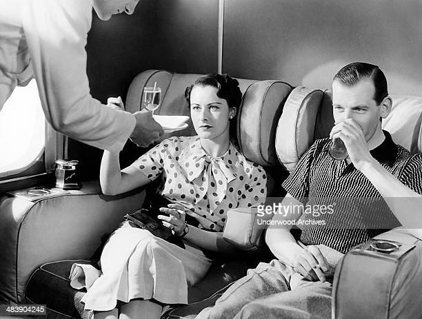 A couple enjoys cocktails in the smoking lounge of the new Imperial Airways Empire flying boat passenger plane London England mid 1930s