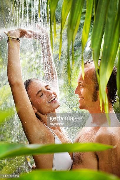 Couple enjoys in a rain on tropical resort.