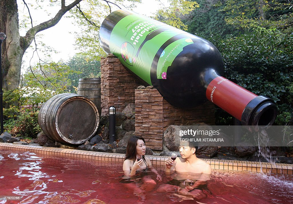 A couple enjoys the 2007 Beaujolais Nouveau wine during the opening of Beaujolais Nouveau spa at the Hakone Yunessun spa resort facilities in Hakone town, Kanagawa prefecture, some 100-kilometre west of Tokyo, 15 November 2007. As Beaujolais Nouveau embargo had passed here, Hakone Yunessun started the annual 11-day-long wine spa to attract visitors.
