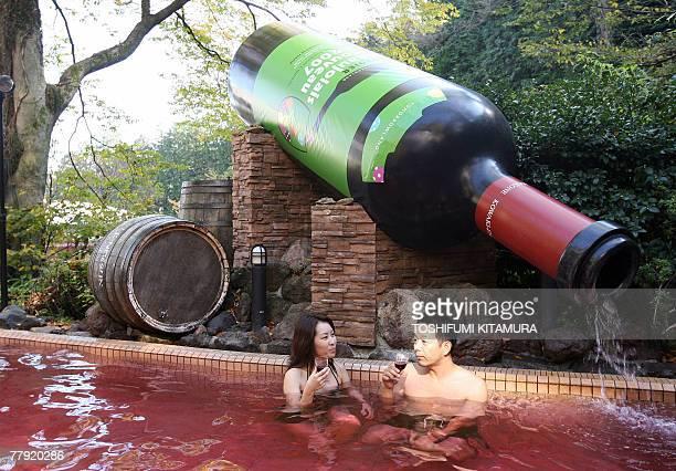 A couple enjoys the 2007 Beaujolais Nouveau wine during the opening of Beaujolais Nouveau spa at the Hakone Yunessun spa resort facilities in Hakone...