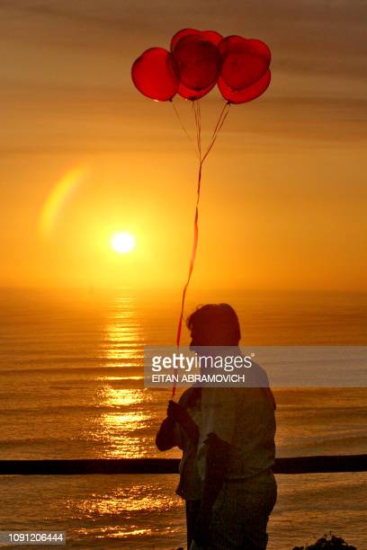 A couple enjoys the sunset carrying ballons in the 'Park of Love' 14 February 2006 in Lima during Valentine's Day AFP PHOTO/EITAN ABRAMOVICH
