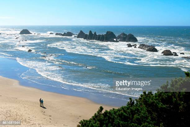 Couple enjoys the view from the beach at Seal Rock State Park on the Oregon coast Seal Rock State Park is located on the central Oregon coast along...