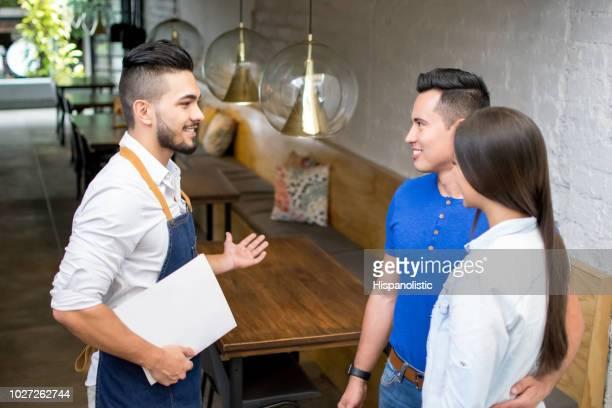 paar invoeren van een restaurant en de ober verwelkomen hen - betreden stockfoto's en -beelden