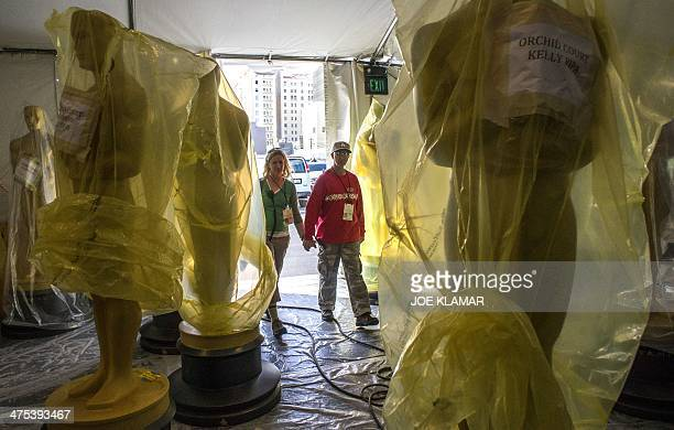 A couple enters a tent where Oscar statues are stored near the Dolby Theater on Hollywood Boulevard February 27 2014 in Hollywood California during...