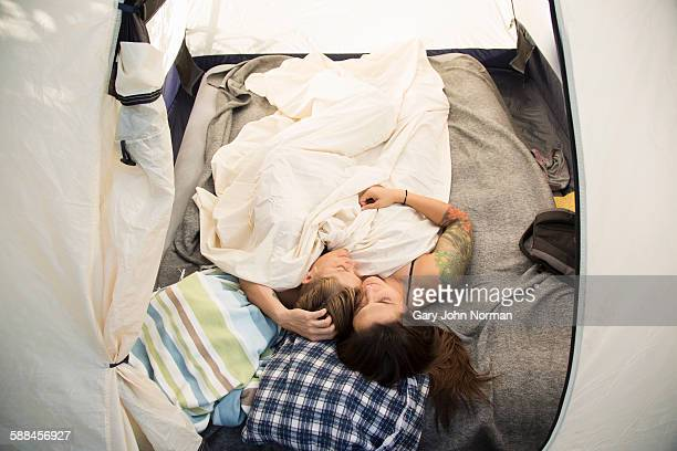 Couple entwined while sleeping in a tent