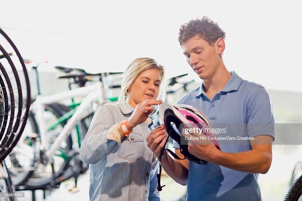 Couple examining bicycle helmet in shop : Stock Photo