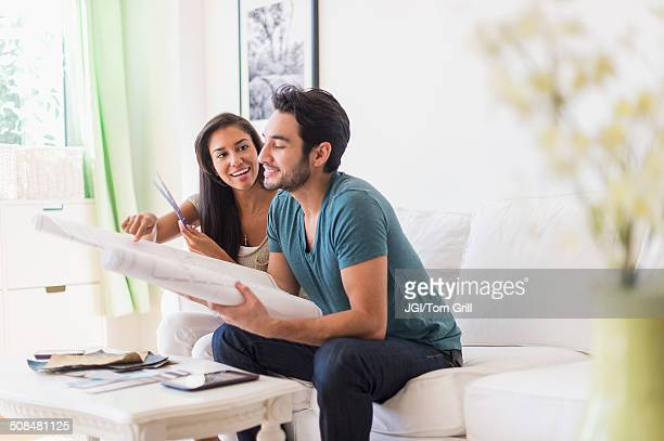 Couple examining blueprints in living room