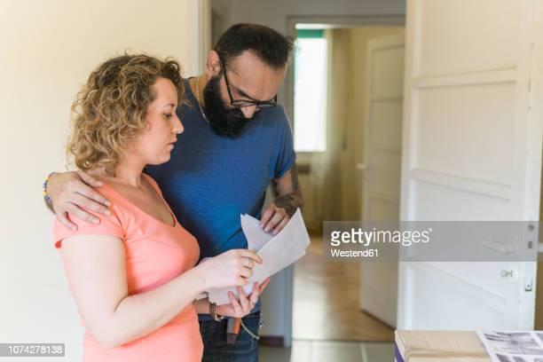 couple examining contract of new home - braço à volta imagens e fotografias de stock