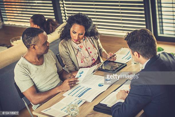 Couple examining insurance papers with agent