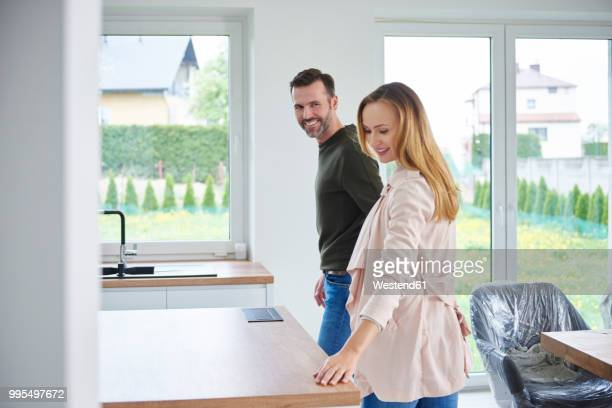 couple examining kitchen in new flat - couples nus photos et images de collection