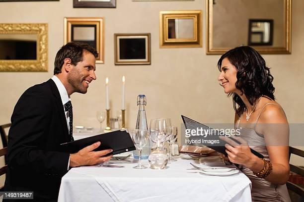 couple examining menus in restaurant - candle light stock pictures, royalty-free photos & images