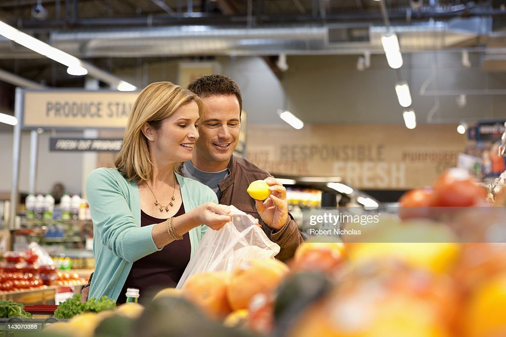 Couple examining produce in supermarket : Stockfoto
