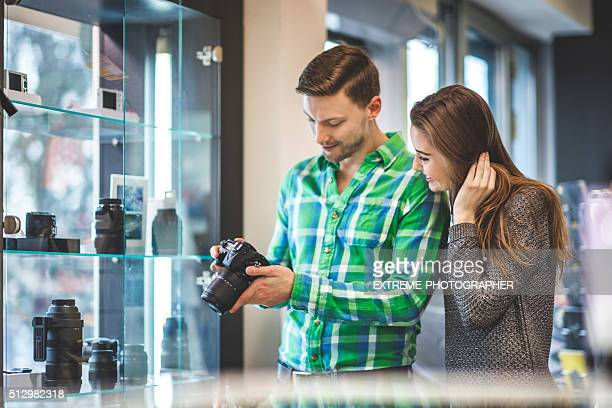 Couple examining SLR camera in the store