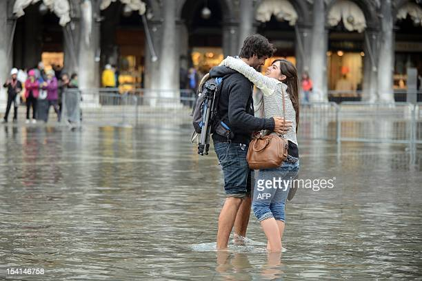 A couple exchanges a kiss while standing barefoot on a flooded St Mark's square during the first acqua alta of the season on October 15 2012 in...