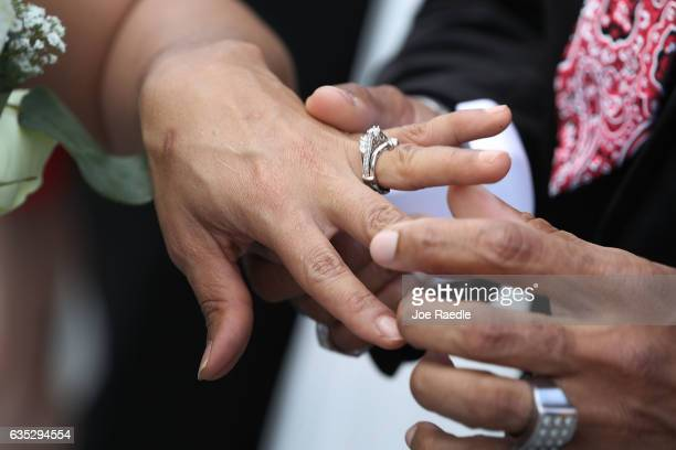 A couple exchanges rings as they participate in a group Valentine's day wedding ceremony at the National Croquet Center on February 14 2017 in West...