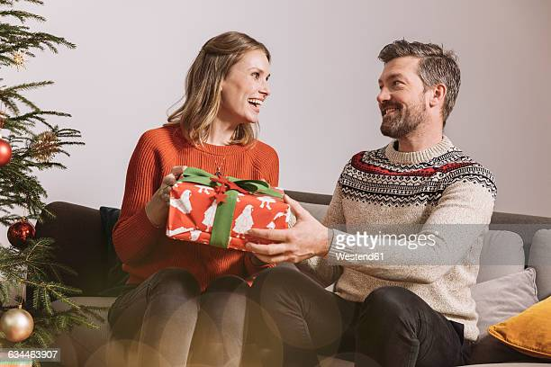 couple exchanging a christmas gift on sofa - gift lounge stock-fotos und bilder