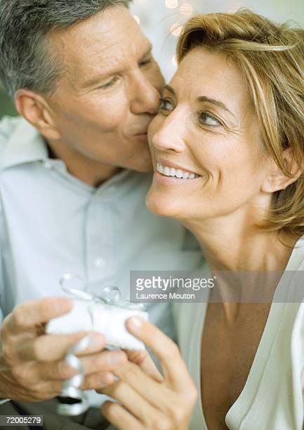 Couple exchanging christmas gift, man kissing woman on cheek