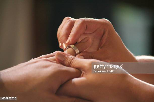 couple exchanging engagement rings - man holding engagement ring stock photos and pictures