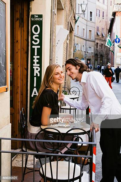 Couple exchanging greetings at osteria , Siena , Italy