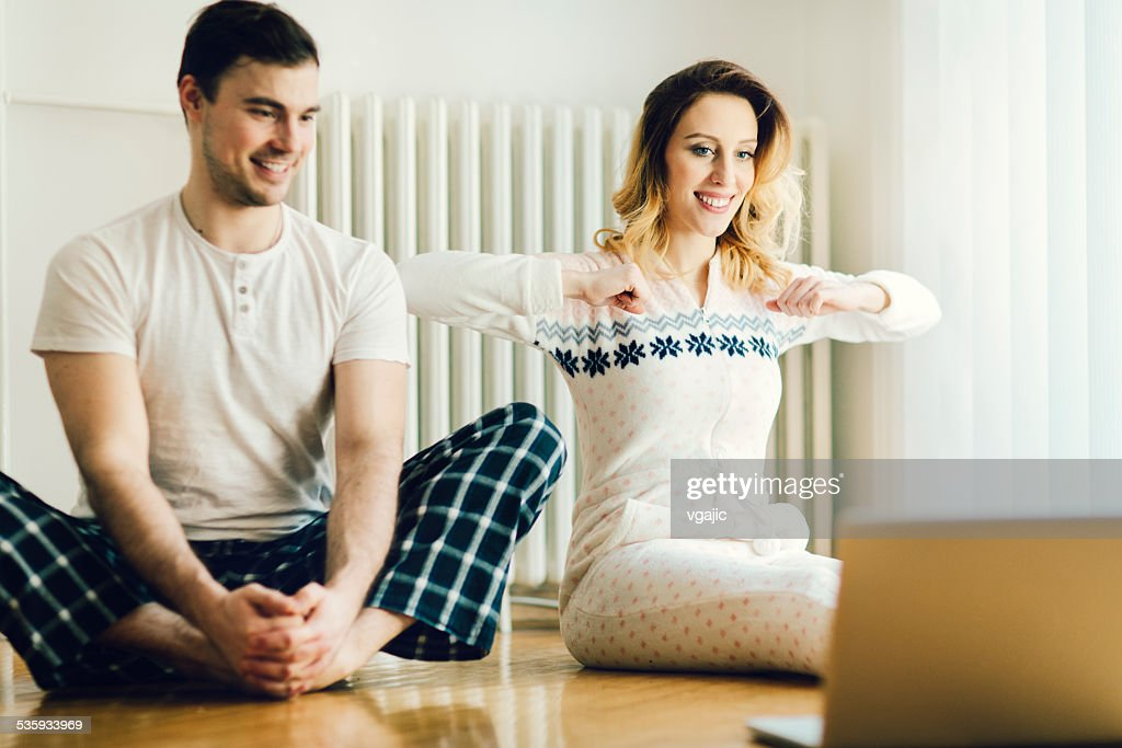 Couple Exercise in a living room with laptop. : Stock Photo
