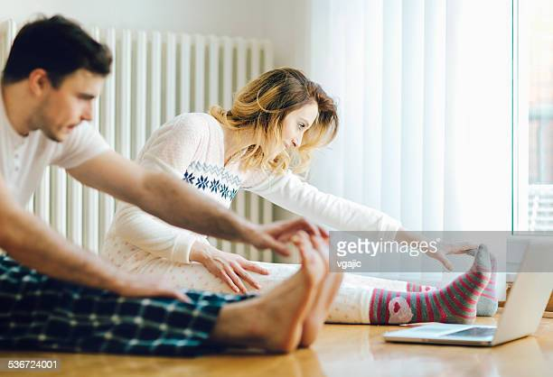 Couple Exercise in a living room with laptop.