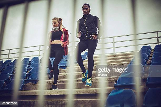 Couple exercise together on the stands at the stadium