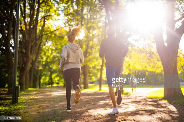 couple exercising in park. - city life stock pictures, royalty-free photos & images