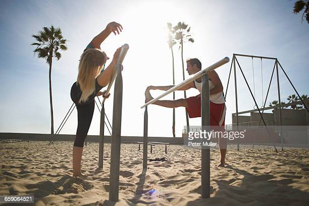 Couple exercising on beach, stretching, using gymnastics parallel bars
